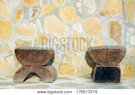 Primitive stools made from sections of tree trunk agains a rough stone wall