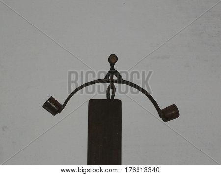 Miniature figure of weight lifter on a black base on gray background
