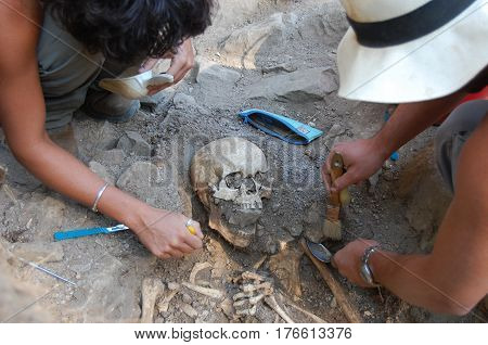 Archaeologist excavating an ancient burial . .