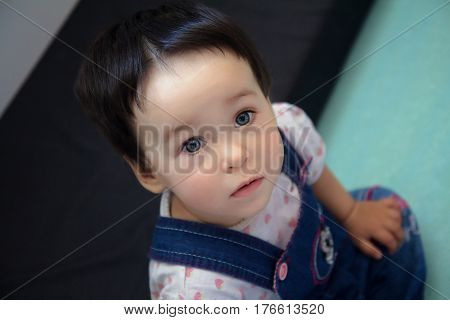 Cute serious one-year-old toddler closeup portrait - sweet sad little baby with beautiful grey eyes