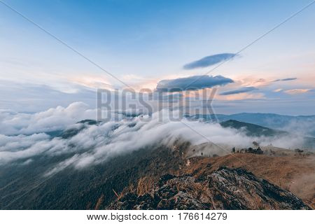 Vintage style beautiful landscape nature of sunrise on peak mountain with cloud fog and sky in winter at Phu Chi Fa Forest Park Chiang Rai Thailand on Sienna-Blue color two tone