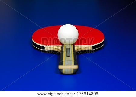 Symmetry of a table tennis. Racket and ball on blue table.