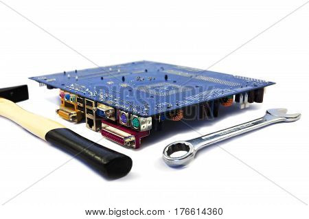 Computer motherboard with big size spanner and hammer on white background. Computer assembling concept.