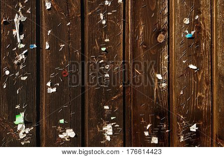 Weathered wooden fence with shreds of notices