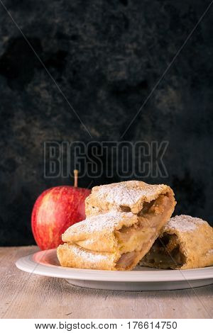 Two Portions Of Apple Strudel With Sugar And With Red Apple