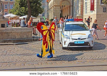 LVIV, UKRAINE - JULY 17, 2015: Man in the costume of butterfly in historical city center, Lviv, Ukraine