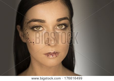 Beautiful girl. Portrait of a girl in makeup beauty on a black background. Woman with make-up beauty. Brunette on a blue background. Beautiful makeup of the girl. Beautiful hair. Portrait of a girl with beautiful hair