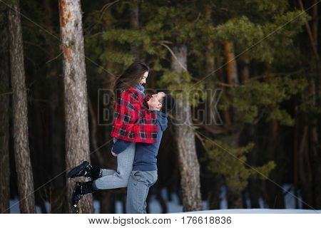 Winter Snow Couple Love Story In The Forest. Happy Romantic Smiling Lovers Hugging In The Snowy Wint