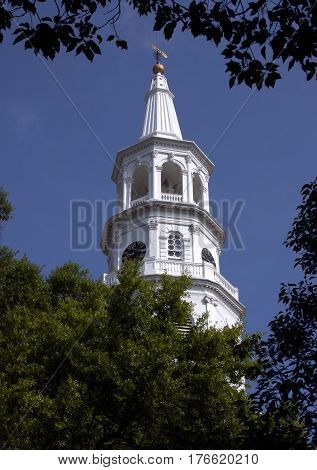 The steeple of St. Michael's Episcopal Church in Charleston SC framed by nearby tree branches.