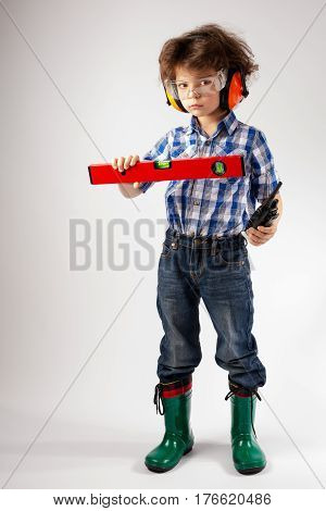 Cute little worker holds a builder's level. Gray background.