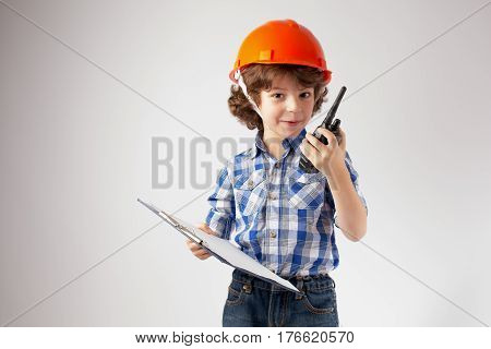 Little curly-haired foreman with a clipboard in his hands directs by radio. Gray background.