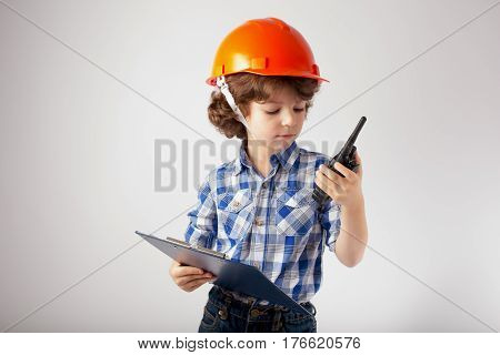 Little curly-haired foreman talking on a walkie talkie. Gray background.