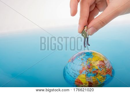 Figurine On The Top Of The Globe In Water