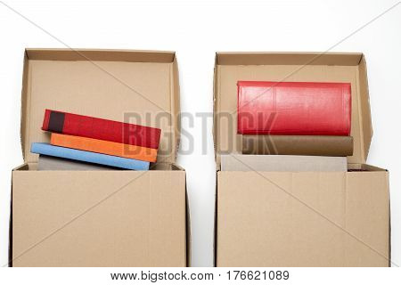 cardboard boxes full of books near the white wall
