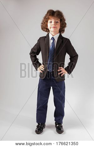 Cute curly-haired boy looks at the camera in a business suit. Full length. Gray background.