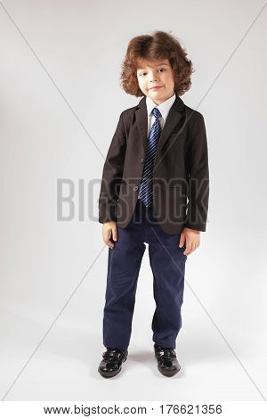 Cute curly-haired boy in a business suit standing at ease. Full length. Gray background.