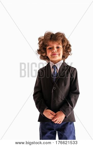 Pleased Curly boy looks at the camera in a business suit. White background.