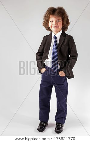 Little curly boy in an unbuttoned jacket standing on the floor. Full length. White background.