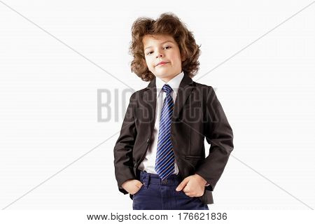Curly trendy boy in a business suit standing and looking at the camera his head thrown back. Hands holding in their pockets. White background.