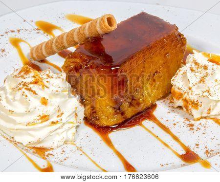 Postre de tocino de cielo en porcion  con nata y barquillo de galleta