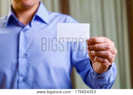 Manager holding visit card. Man showing blank business card. Person in blue shirt. Mock up design.