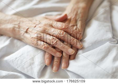 Tired senior's hands on the bed. Old hands