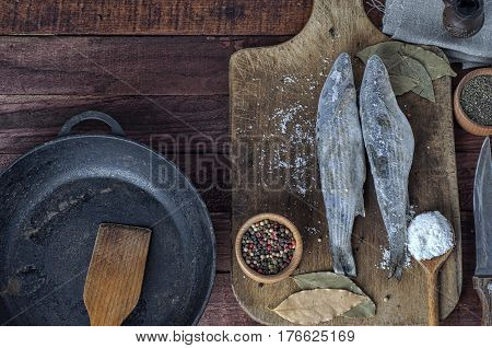 Frozen fish smelt on the kitchen board spices and black cast-iron frying pan