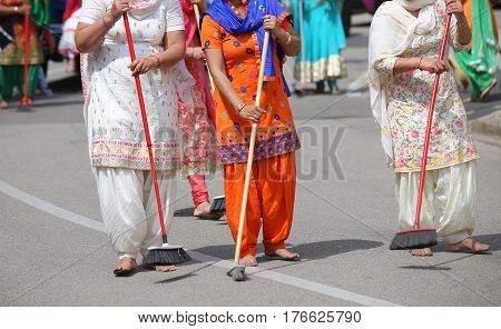 Sikh women while scavenging the street with a broom during a Sikh festival