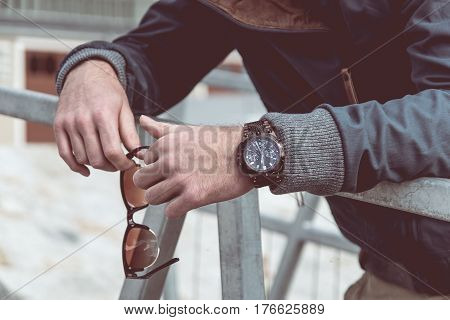 Luxury men's watch and fancy sunglasses in man hands