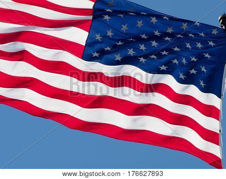 American flag waving in wind with blue sky background.