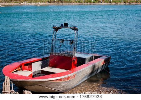 Weathered metal boat with red paint in water.