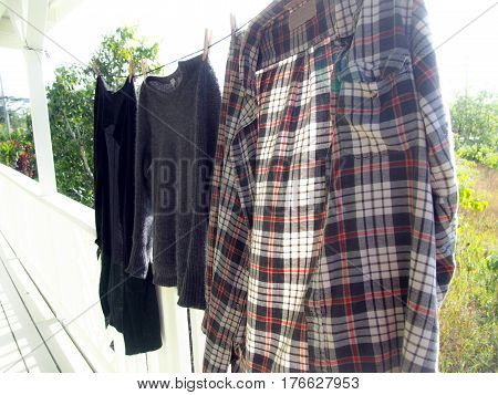 A flannel shirt and two other sweaters hanging on a clothesline in the sun.