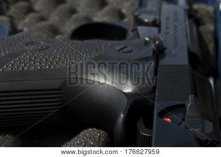 A closeup of a black gun in a case lined with foam.