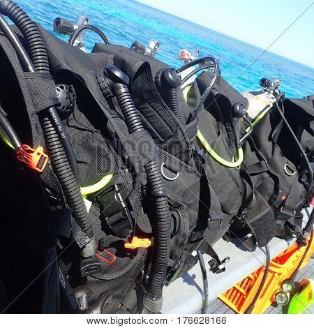 Several sets of scuba gear prepared for a dive.