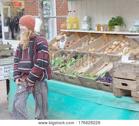 LEWES GREAT BRITAIN - FEB 25 2017: Smiling woman selling vegetables like potato carrot salad and onion and pumkin in boxes made of wood. . February 25 2017 in Lewes Great Britain