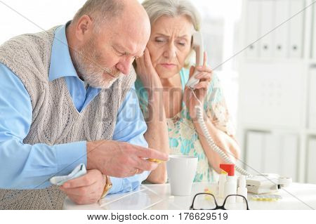 Concerned elderly senior couple with pills and on the phone