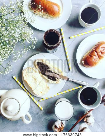 Breakfast flat lay with flowers, coffee, teapot, milk, chocolate spread and sweet buns. Knolling.