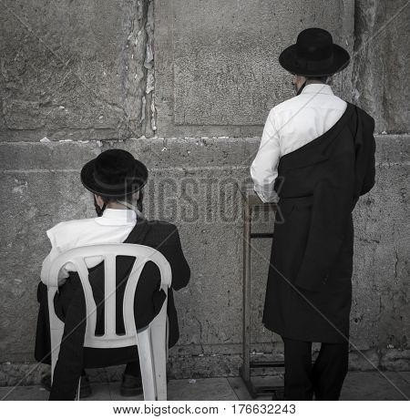 JERUSALEM, ISRAEL - MARCH 06, 2017: Two men praying at the men's section of the Wailing (Western) Wall in the old town Jerusalem