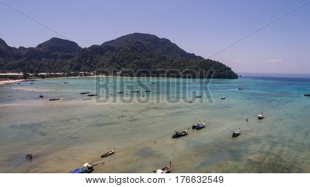 Aerial drone photo of boats on the sea during ebb tide on iconic tropical beach  of Phi Phi island, Thailand