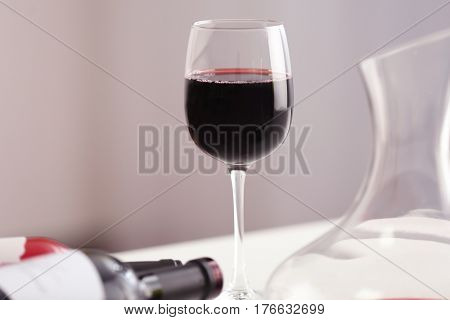 Wineglass and bottles of red wine on light background