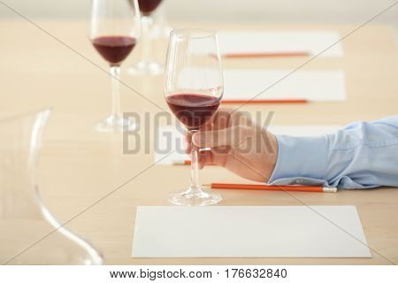 Sommelier estimating red wine in wineglass at tasting