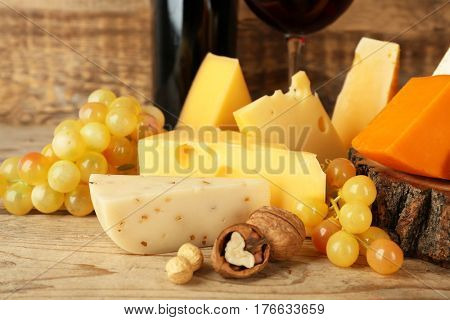 Red wine and stump with variety of cheese on wooden background
