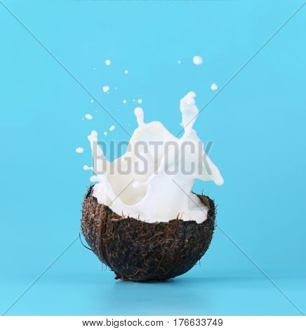 Cracked coconut with splashes of milk on color background