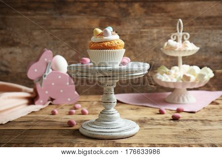 Tasty Easter cupcake on cake stand against wooden background