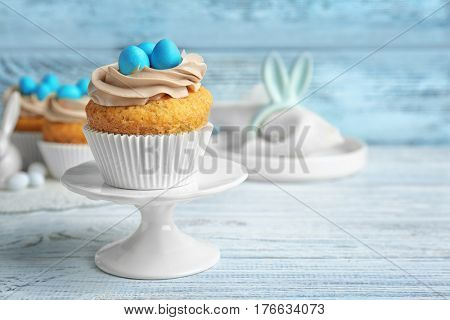 Cake stand with delicious Easter cupcake on wooden table