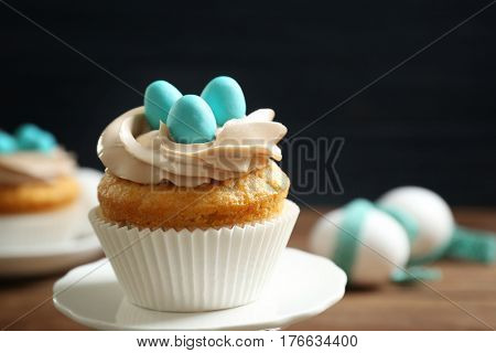 Delicious Easter cupcake on cake stand against dark background