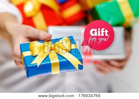 Male hands holding a gift boxes. Presents wrapped with ribbon and bow. Gift for you speech bubble. Man in white shirt give box.