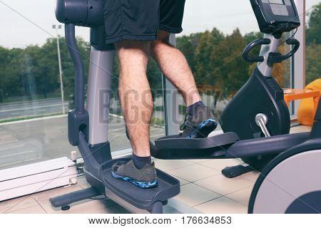 Man using elliptical trainer in gym