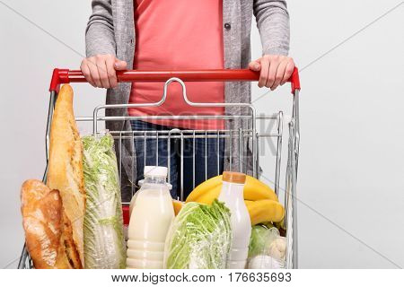 Young woman with full shopping pushcart on light background