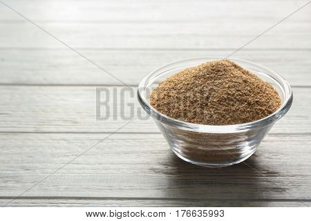 Glass bowl of bread crumbs on white wooden table